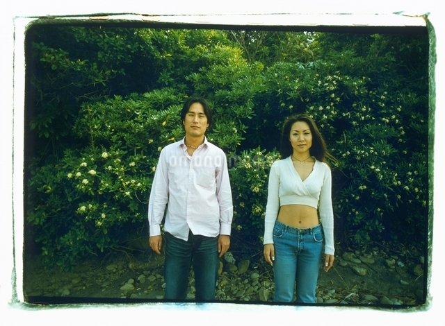 森林の前に立つ日本人カップルの写真素材 [FYI03207228]