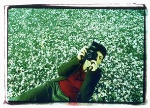 桜の花びらの上でカメラを構える外国人女性の写真素材 [FYI03207229]