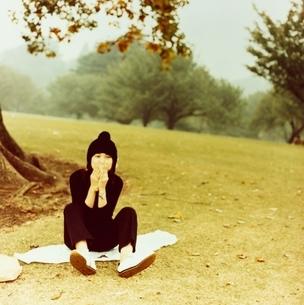 草原に座るニット帽子の日本人女性と木の写真素材 [FYI03207254]