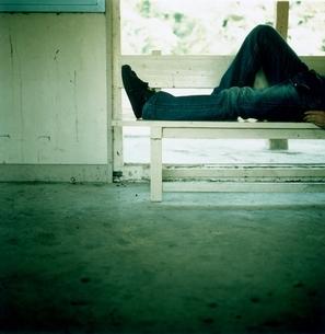 駅のベンチに寝そべる日本人男性の写真素材 [FYI03207261]