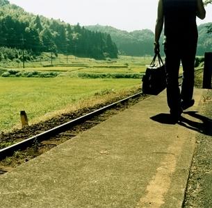 駅のホームを歩く日本人男性の写真素材 [FYI03207262]
