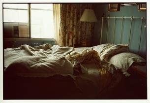 乱れたシーツと枕のベッドとランプの写真素材 [FYI03207269]