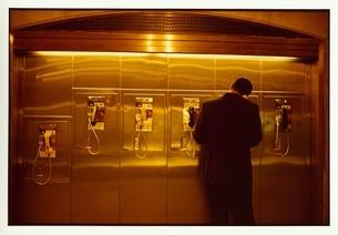 公衆電話で電話をかける男性の写真素材 [FYI03207276]