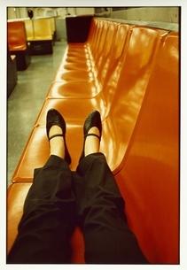 ベンチ(オレンジ色)に座る女性の脚の写真素材 [FYI03207282]