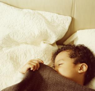 ベッドで寝ている男の子の写真素材 [FYI03207307]