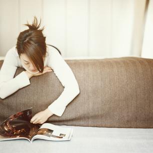 '雑誌を見ながらリラックスする日本人女性の写真素材 [FYI03207315]