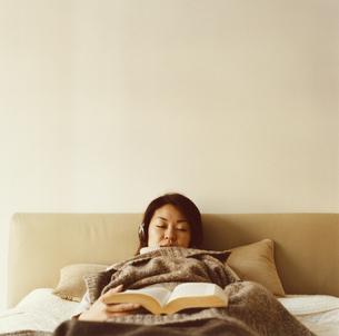 ベッドで昼寝をする日本人女性と本の写真素材 [FYI03207321]
