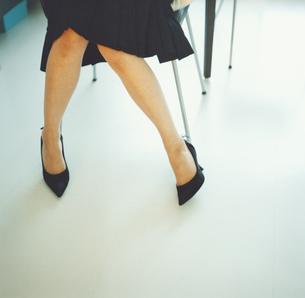 ハイヒールを履いて座った女性の足の写真素材 [FYI03207331]