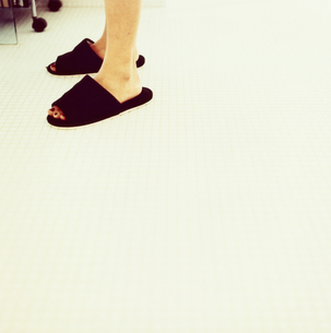 タイルの床に立つスリッパを履いた足の写真素材 [FYI03207335]