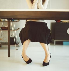 ハイヒールを履いて座った女性の足の写真素材 [FYI03207336]