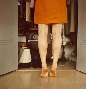 クローゼットの洋服を選ぶ女性の後ろ姿の写真素材 [FYI03207344]