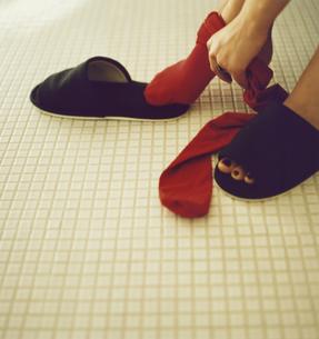 靴下(赤)を履く足とスリッパの写真素材 [FYI03207353]