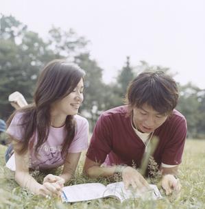 芝生に寝転び雑誌を読む日本人カップルの写真素材 [FYI03207371]