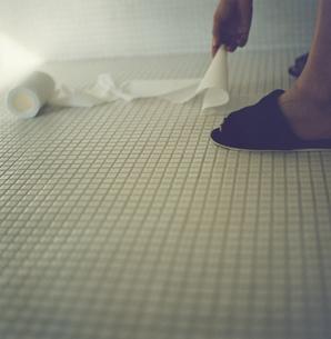 タイルの床のトイレットペーパーを拾う手とスリッパを履いた足の写真素材 [FYI03207372]