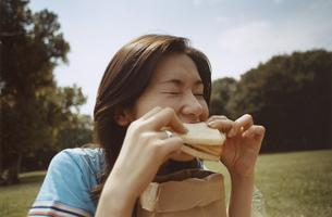 公園でサンドイッチを食べる日本人女性の写真素材 [FYI03207373]