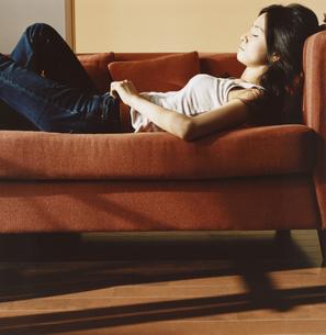 ソファーに寝転ぶ日本人女性の横顔の写真素材 [FYI03207376]