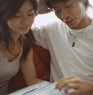 雑誌を読む日本人カップルの写真素材 [FYI03207385]