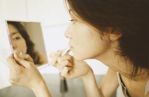 手鏡を見ながら化粧する日本人女性の写真素材 [FYI03207394]