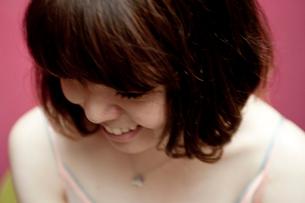 うつむいて笑うボブヘアの20代女性の写真素材 [FYI03207495]