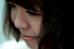 うつむいて笑うそばかすのあるボブヘアの20代女性の写真素材 [FYI03207498]