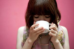 ピンク色のストールを巻いてコーヒーを飲むボブヘアの20代女性の写真素材 [FYI03207508]