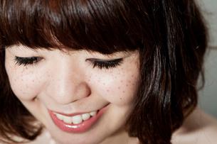 うつむいて笑うそばかすのあるボブヘアの20代女性の写真素材 [FYI03207517]