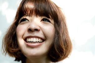 上を向いて笑うまつげの長い20代女性のアップの写真素材 [FYI03207524]