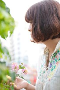 ピンクと黄色の花を触るボブヘアの20代女性の写真素材 [FYI03207527]