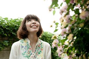 路地裏で花を眺めるボブヘアの20代女性の写真素材 [FYI03207528]