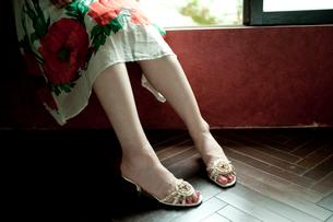 窓辺に座るサンダルを履いた女性の足元の写真素材 [FYI03207532]