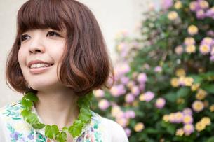 ピンクと黄色の花の横で笑うボブヘアの20代女性の写真素材 [FYI03207535]