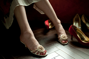 窓辺に座るサンダルを履いた女性の足元とヒール靴の写真素材 [FYI03207537]