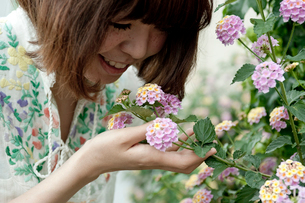 ピンクと黄色の花の匂いを嗅ぐボブへアの20代女性の写真素材 [FYI03207539]