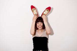 赤い靴を頭に乗せてバニーガールの真似をする20代女性の写真素材 [FYI03207544]