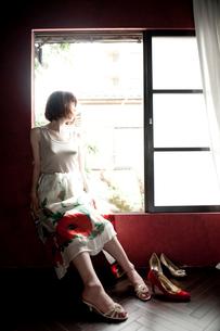 窓辺に座ったスカートをはいている女性とヒール靴の写真素材 [FYI03207548]