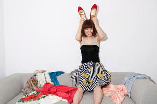 服の広がったソファに座り赤い靴を頭に乗せる20代女性の写真素材 [FYI03207555]
