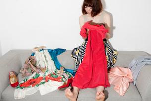 ソファに座って服を選んでいる20代女性の写真素材 [FYI03207557]