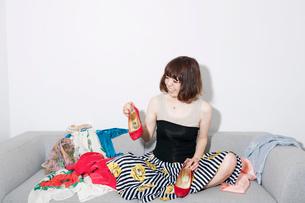 服の広がったソファに座ってヒール靴を持つ20代女性の写真素材 [FYI03207558]