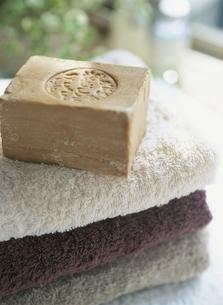 重なる3枚のタオルの上に置かれた石鹸の写真素材 [FYI03207591]