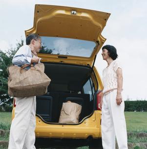 自動車のトランクから荷物を運ぶ日本人中高年夫婦の写真素材 [FYI03207943]