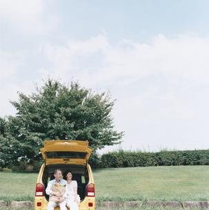 自動車のトランクに腰掛ける日本人中高年夫婦の写真素材 [FYI03207947]