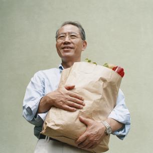 買い物袋を抱えた日本人中高年男性の写真素材 [FYI03207951]