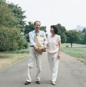 買い物袋を抱え公園を歩く日本人中高年夫婦の写真素材 [FYI03207953]
