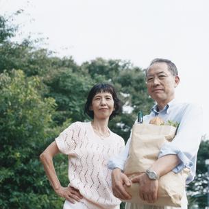 買い物袋を抱えた日本人中高年夫婦の写真素材 [FYI03207955]