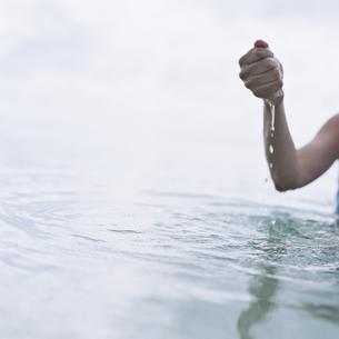 海の水をすくう女性の手の写真素材 [FYI03207960]