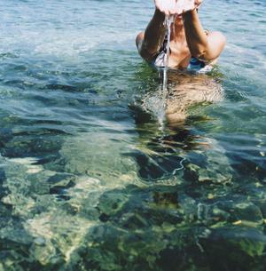 海の水をすくう女性の写真素材 [FYI03207982]