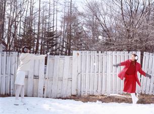 雪玉を投げる日本人女性と白い塀の写真素材 [FYI03208104]