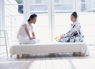 ベッドの上で正座する日本人男性と女性の写真素材 [FYI03208574]