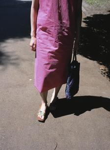 ピンク色のワンピースとサンダルの女性の足元の写真素材 [FYI03208622]