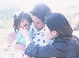 泣いている女の子を慰める父親と母親の写真素材 [FYI03208661]